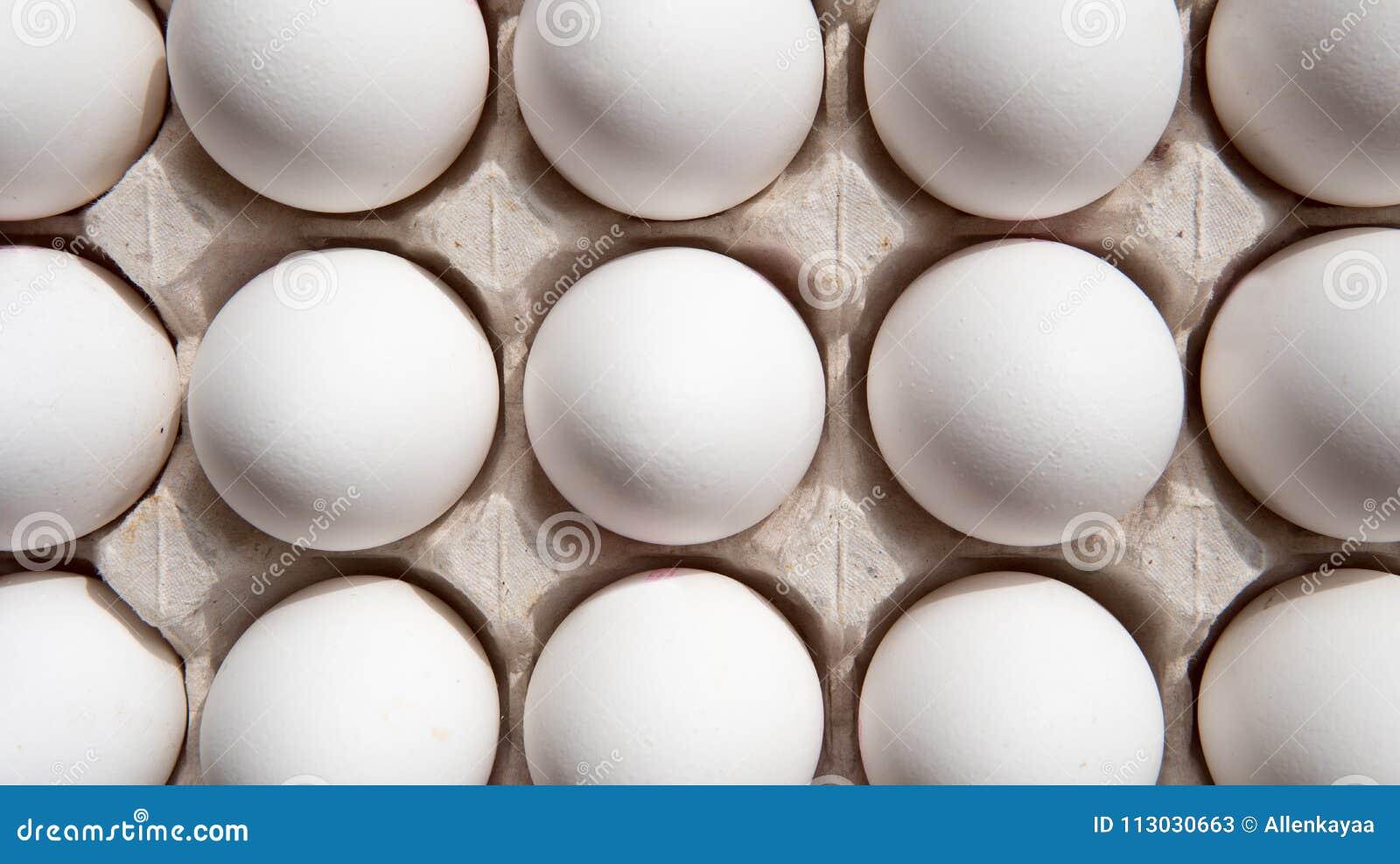 Huevos blancos en una opinión superior de la caja
