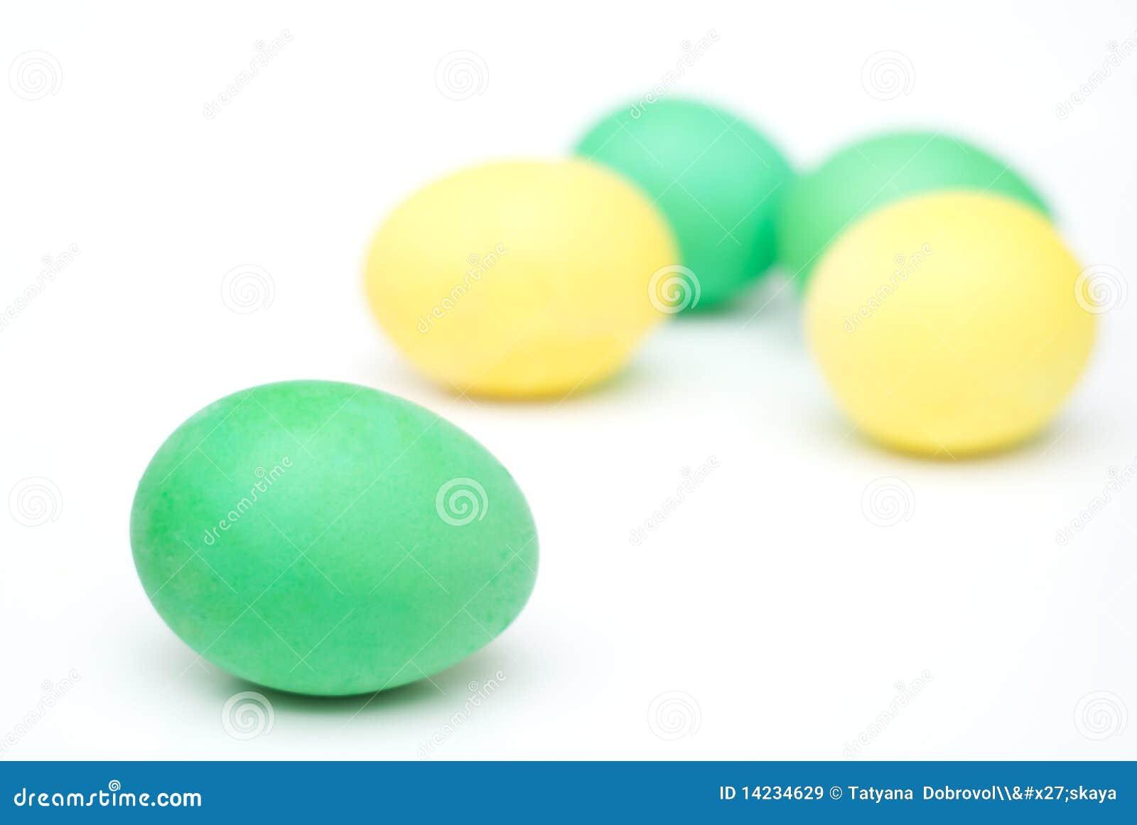 Huevos de Pascua amarillos y verdes aislados en blanco