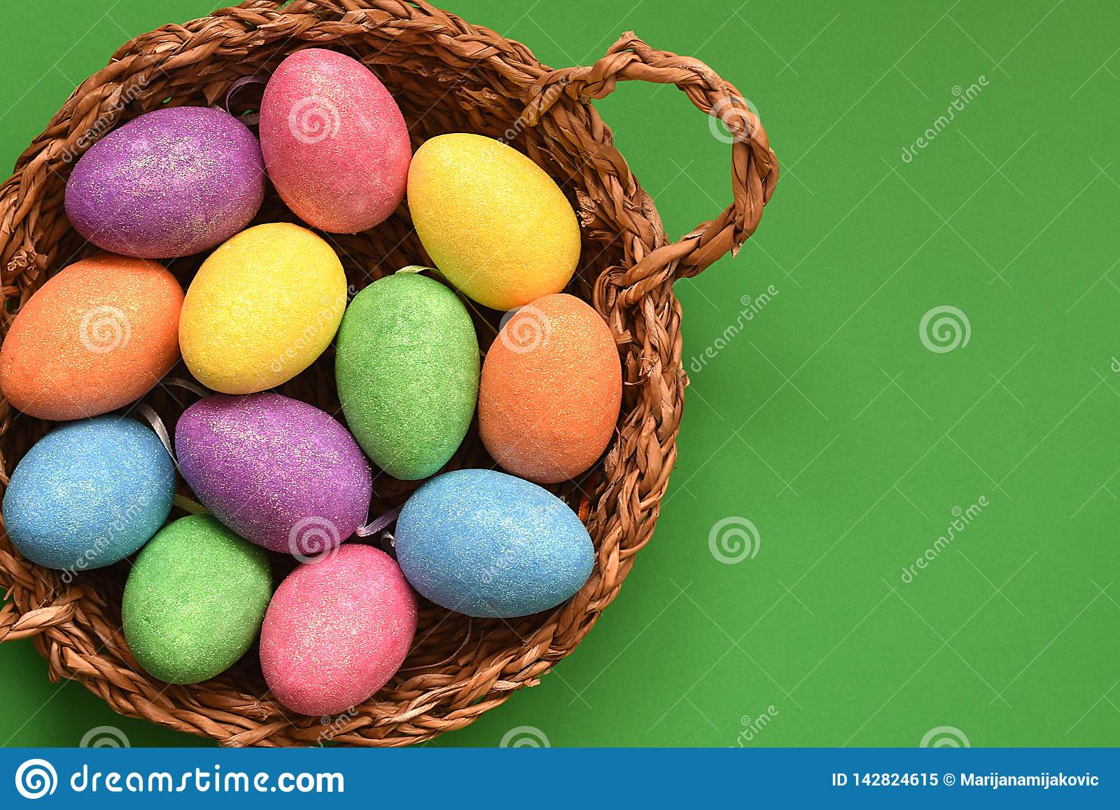 Huevos de Pascua coloreados chispeantes del caramelo que brillan en una cesta de mimbre, visión superior, fondo verde