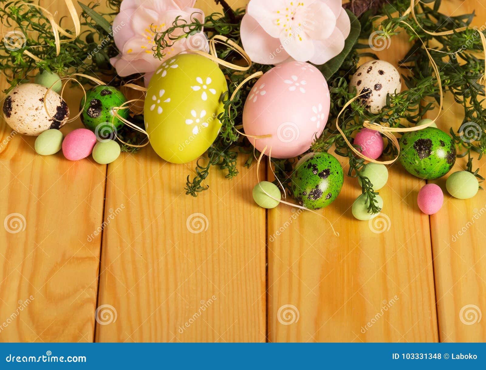 Huevos de Pascua coloreados, flores, cinta del caramelo, contra el contexto PAL