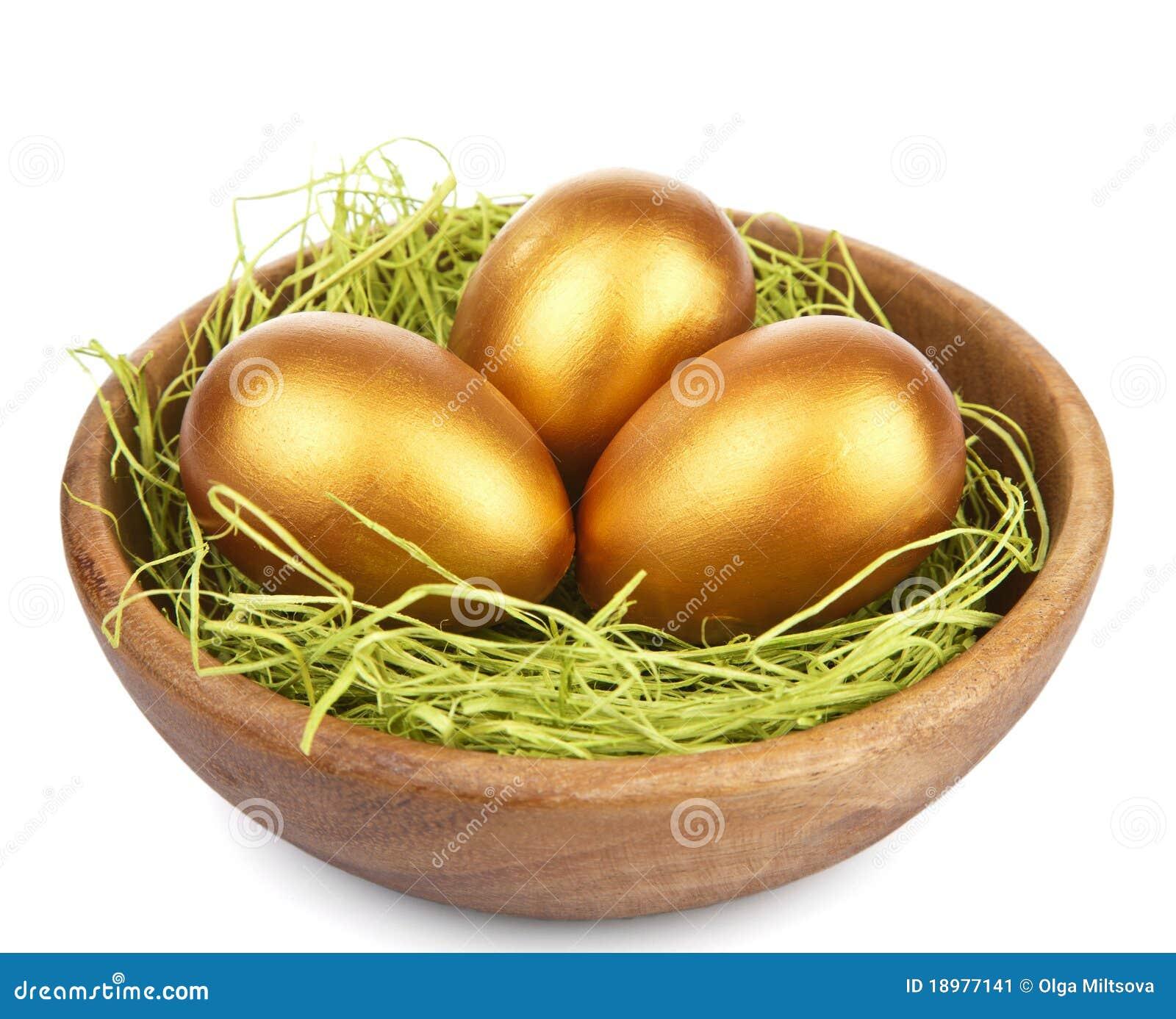 Huevos de Pascua de oro en el tazón de fuente aislado