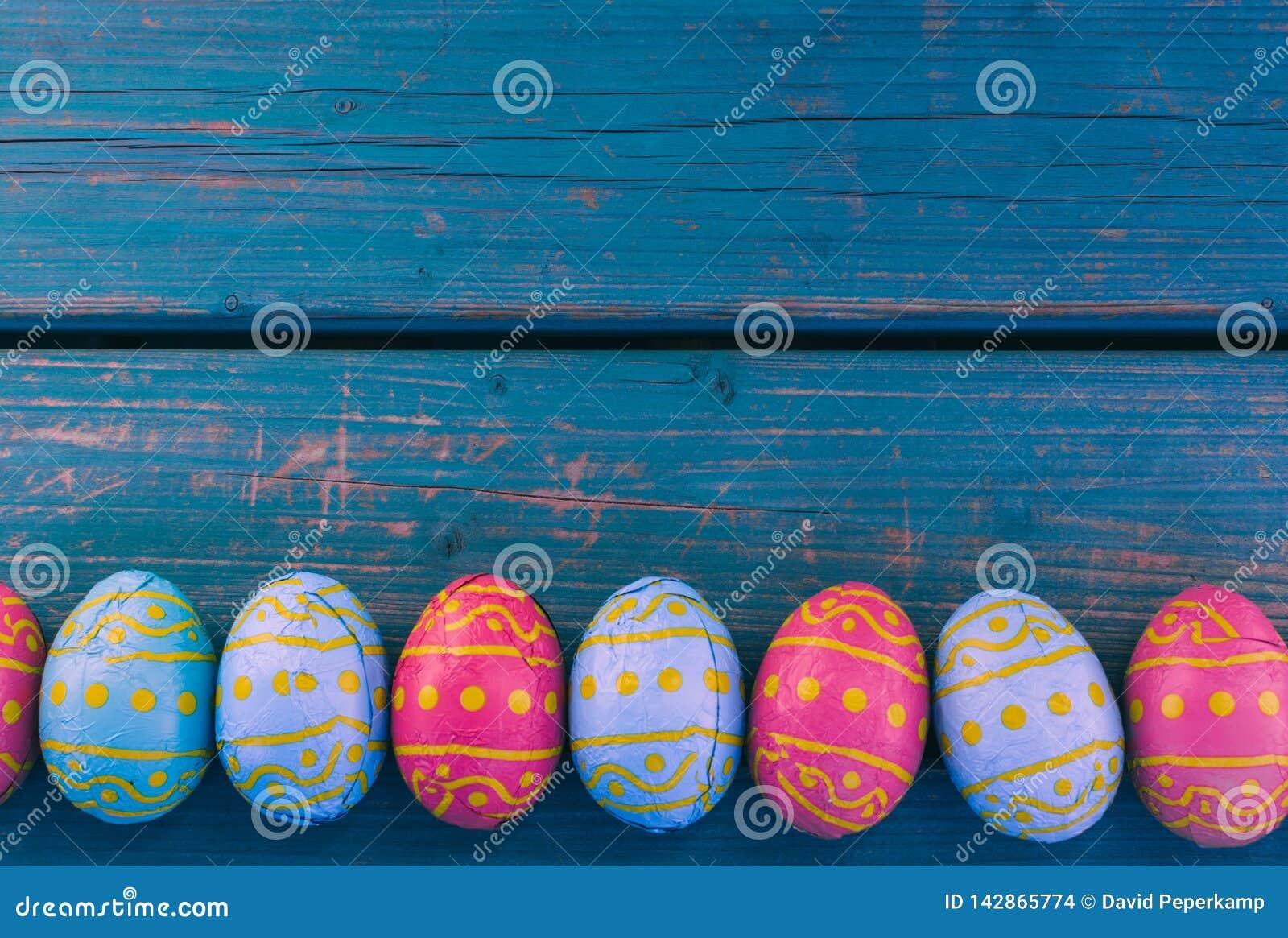 Huevos de Pascua del chocolate en fila, banco azul, fondo de pascua