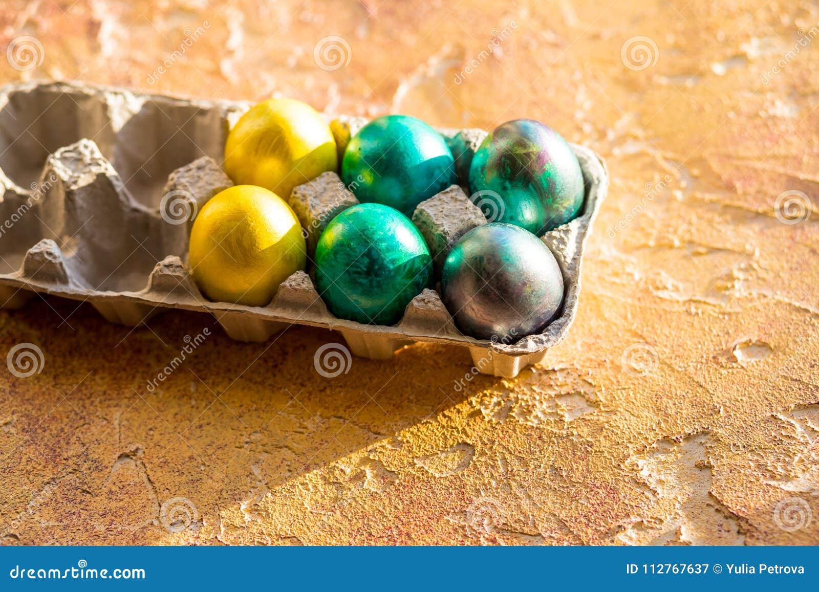 Huevos de Pascua en la tabla amarilla Fondo del día de fiesta Esquina de una bandeja de huevos coloridos Concepto feliz de Pascua