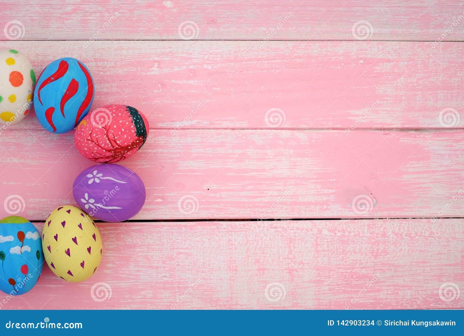 Huevos de Pascua pintados a mano en colores pastel con el fondo rosado