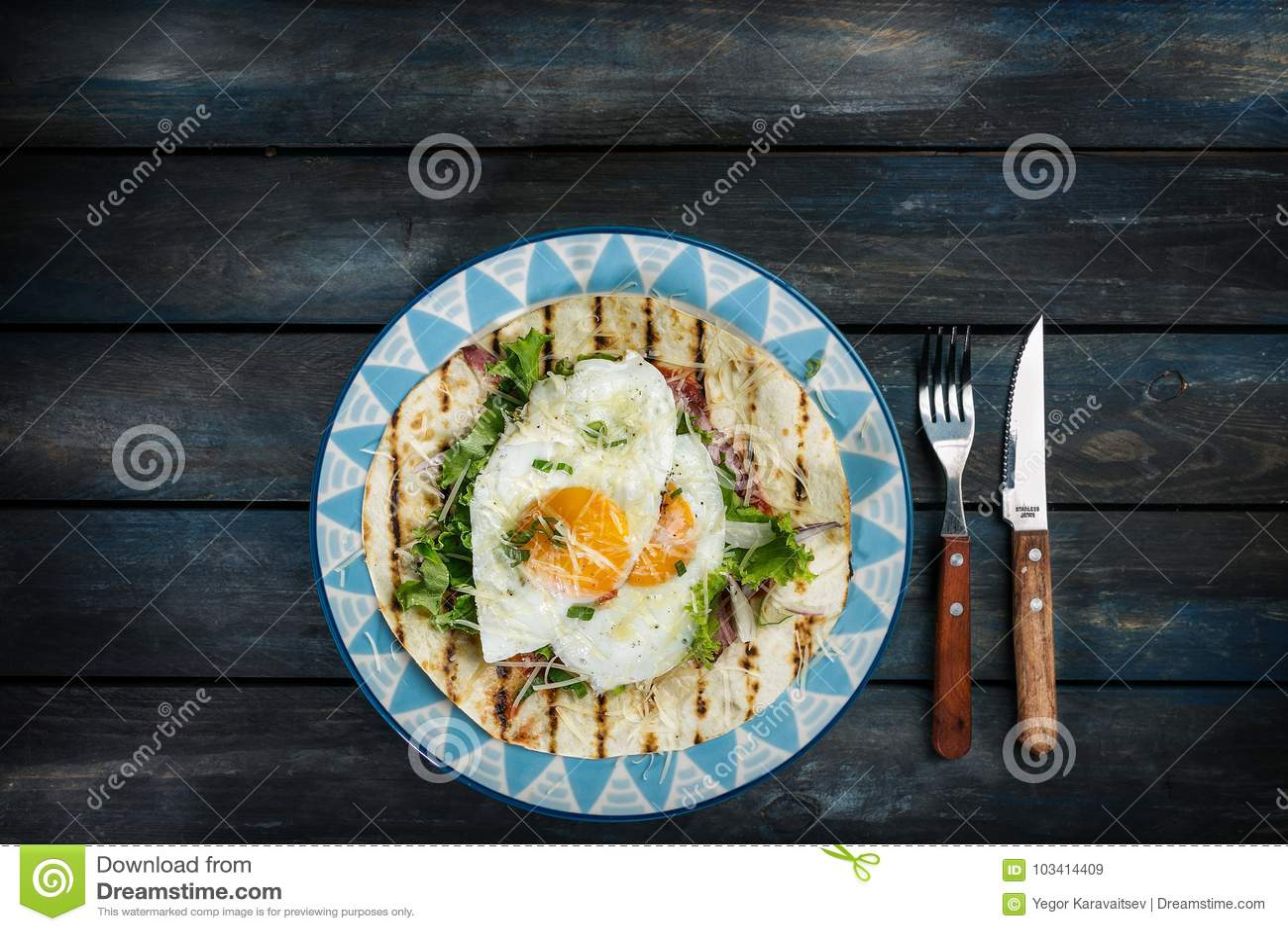 Huevos fritos en la tortilla de la harina con la ensalada verde y el queso Idea útil del desayuno o del almuerzo Cuchillo de la b
