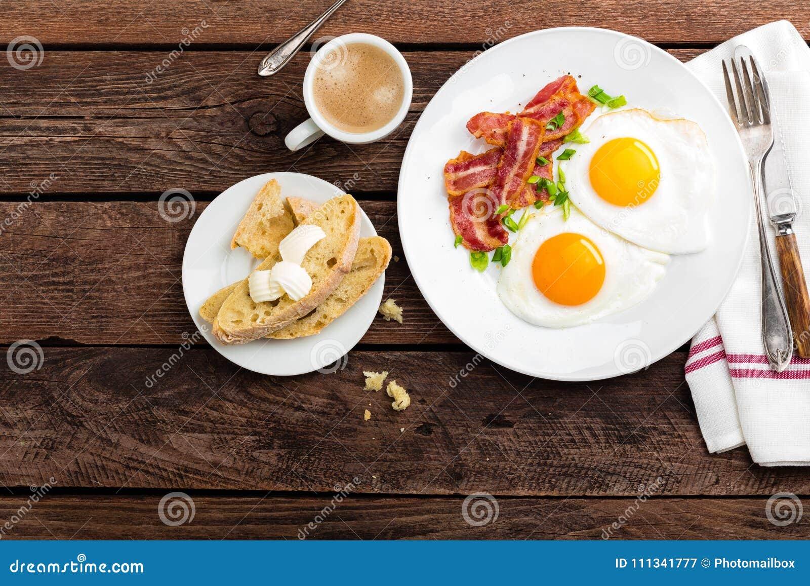 Huevos fritos, tocino y pan italiano del ciabatta en la placa blanca Taza de café Opinión superior del desayuno Fondo de madera