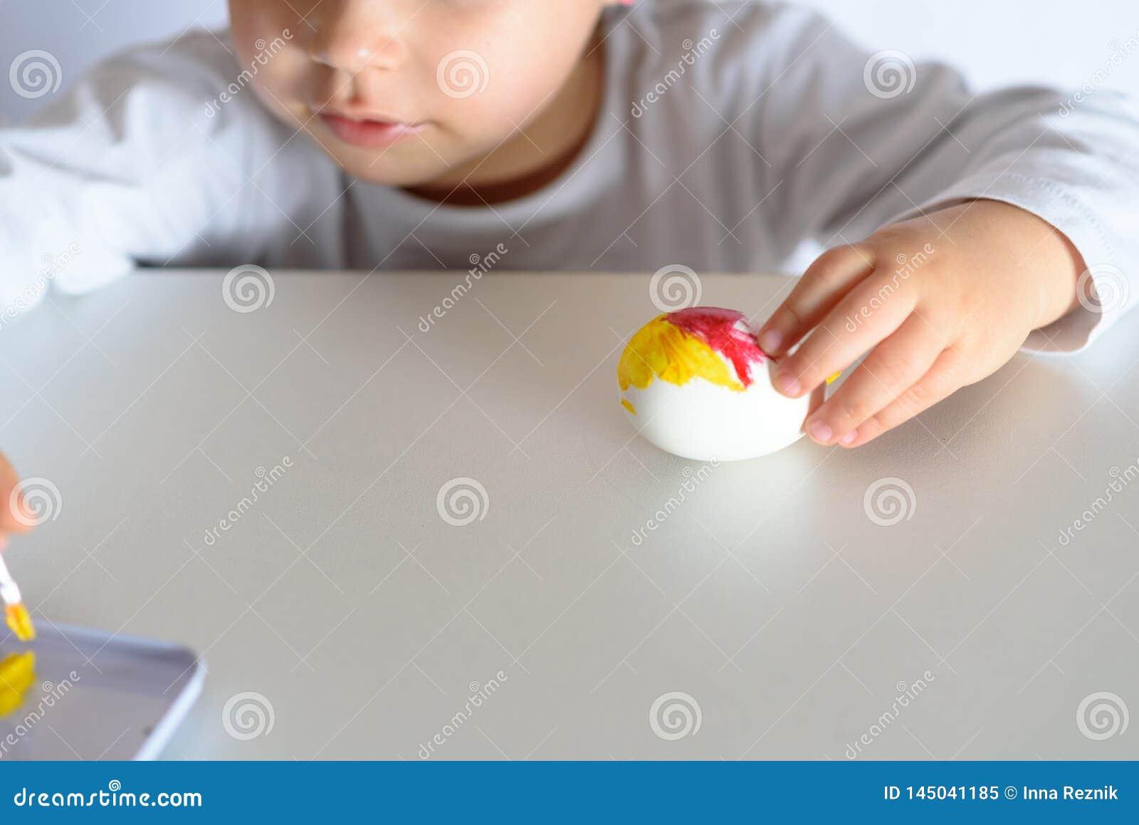 Huevos que colorean por el tiempo de pascua en casa