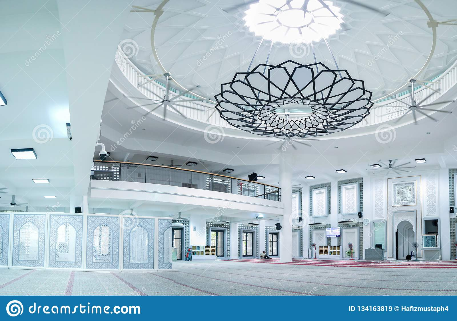 Huge hall of the mosque with modern minimalist chandelier at the center