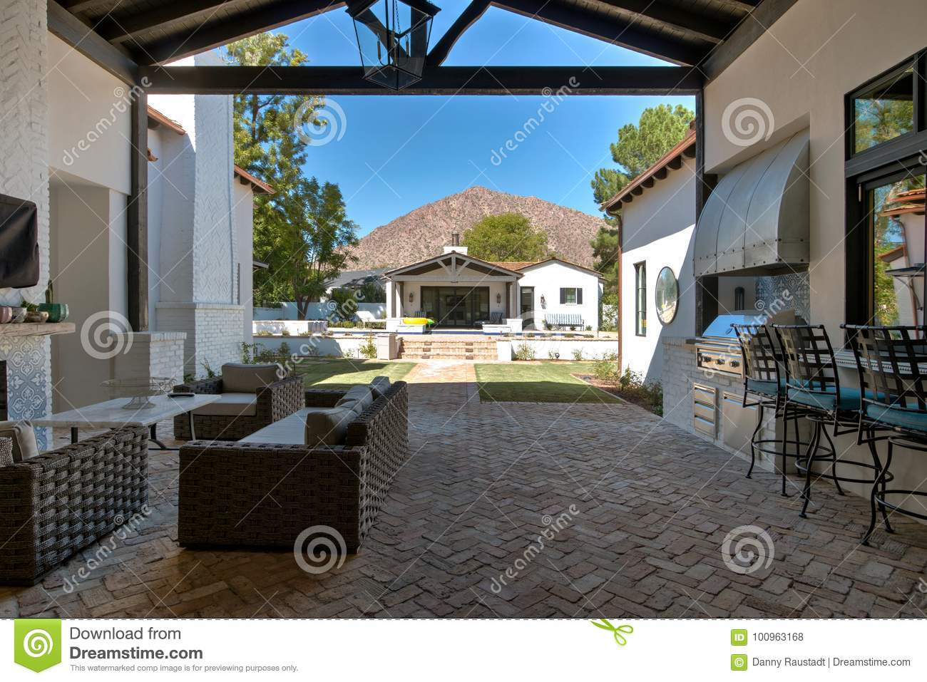 Huge mansion home sliding glass doors open to a large outdoor patio with a barbeque grill bar fireplaces and big screen tv