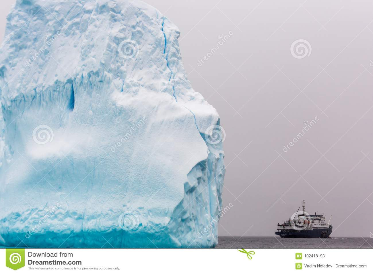 Huge piece of iceberg with antarctic cruise ship at the horizon, Antarctica