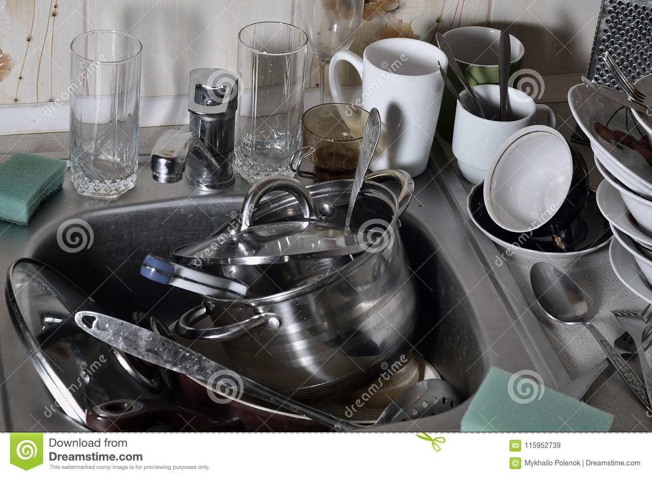 A huge pile of unwashed dishes in the kitchen sink and on the countertop. A lot of utensils and kitchen appliances before washing
