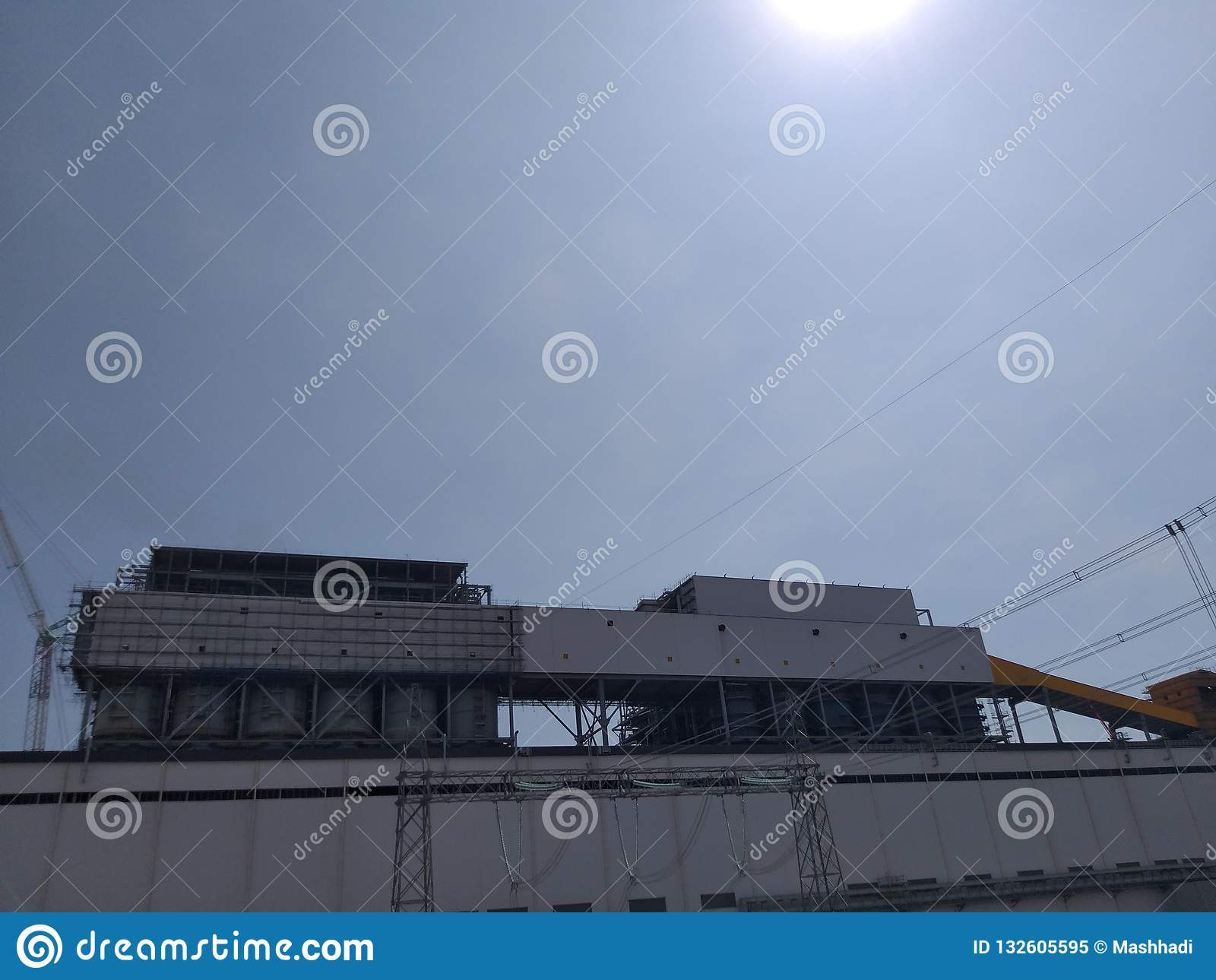 A huge steel structure building under the shining sun and blue sky