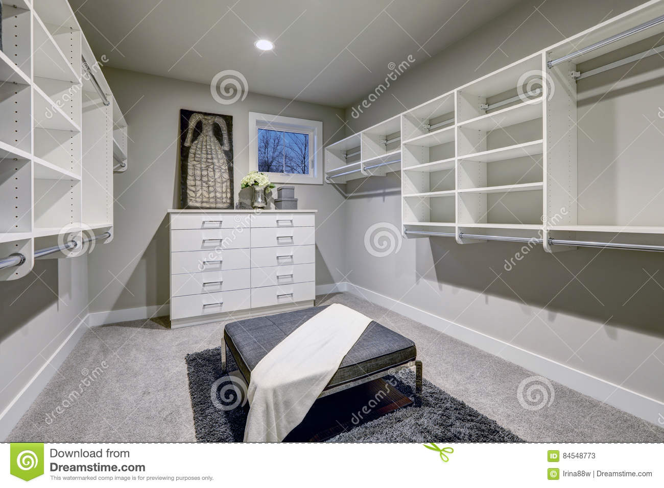 Huge Walk In Closet With Shelves, Drawers And Gray Bench.