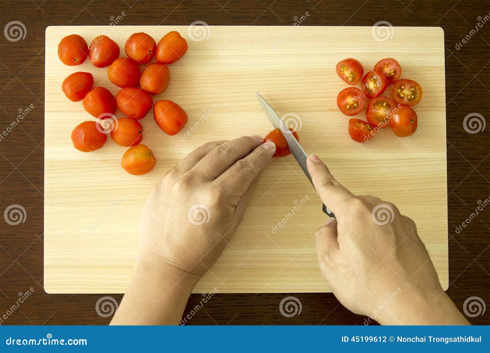 Hugga av Cherry Tomato på skärbräda