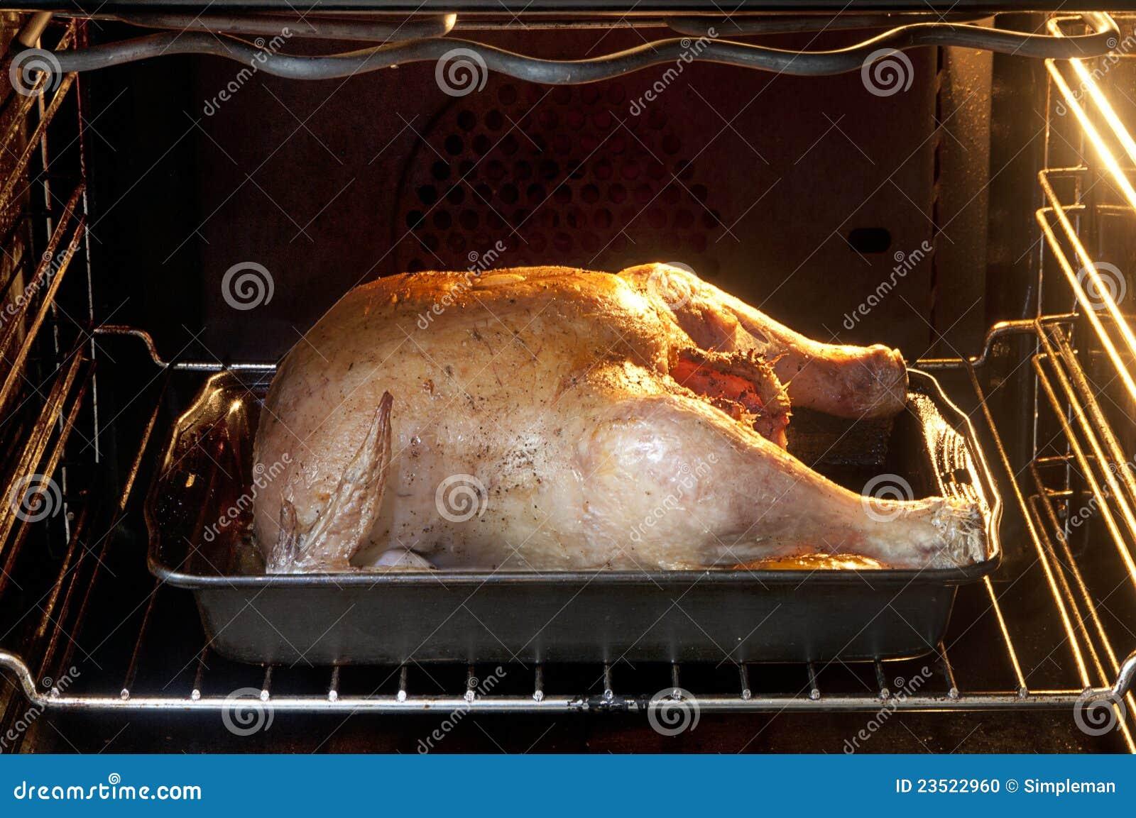Gebratenes huhn das im schwarzen ofen kocht