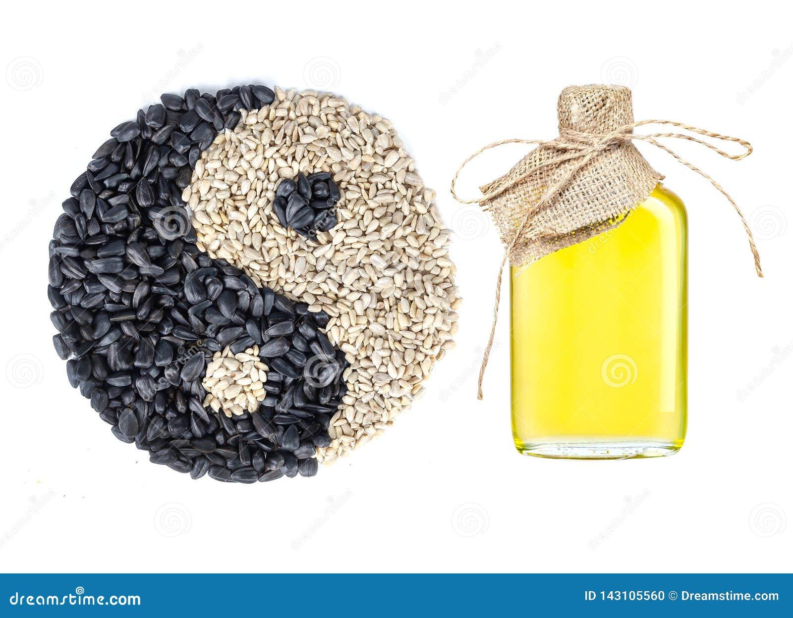 Huile de tournesol dans une bouteille en verre ouvrée et un symbole de yin et de yang faits de graines sur le backgound blanc