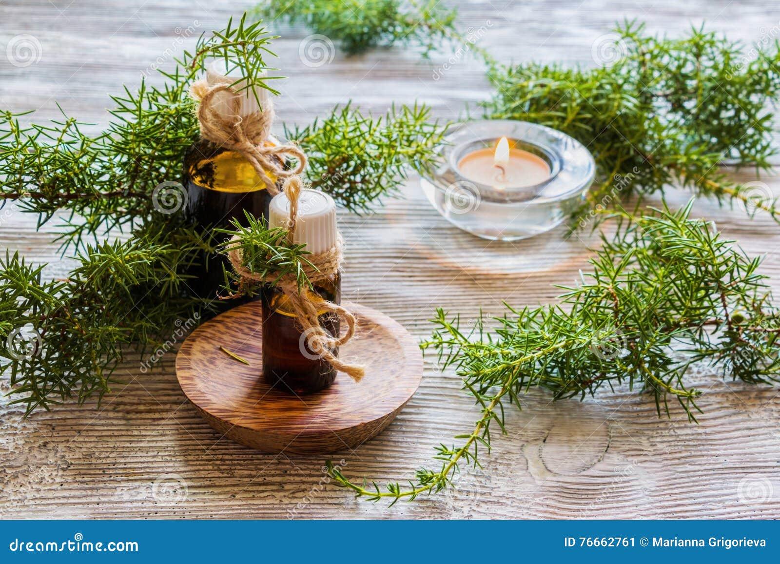 Huile essentielle de genévrier dans une bouteille en verre sur une table en bois Utilisé dans la médecine, les cosmétiques et l a