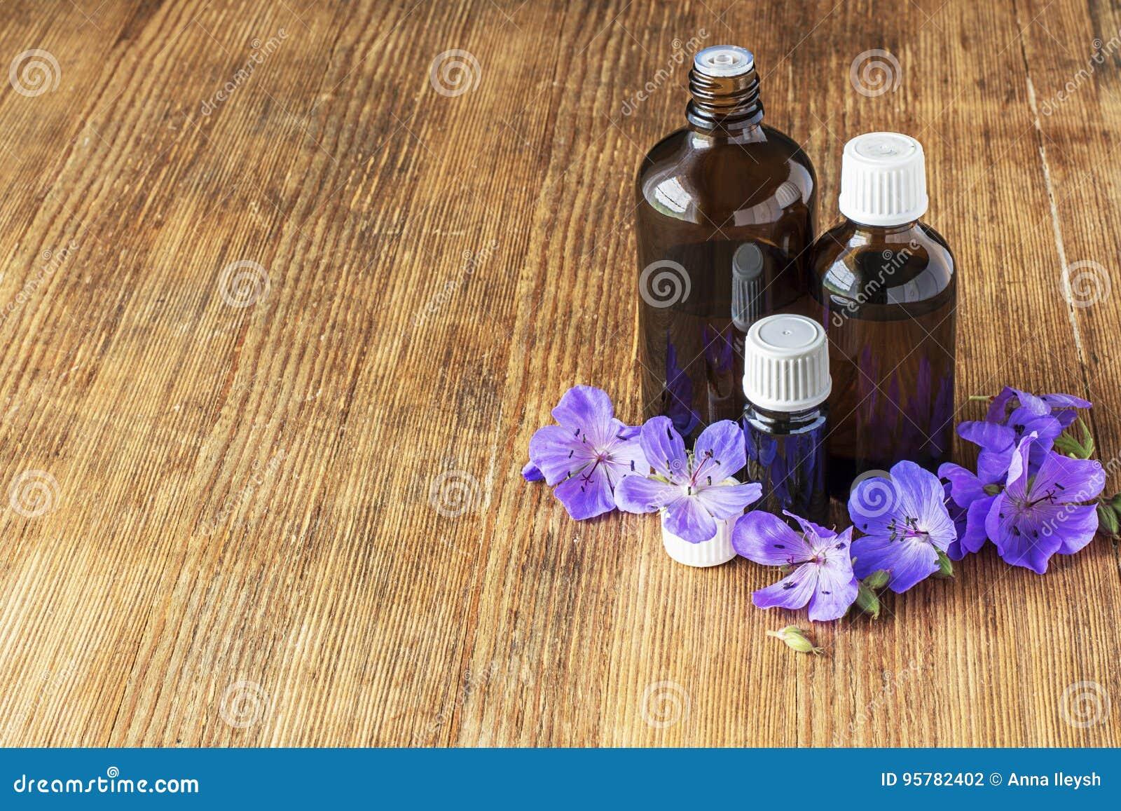 Huile essentielle de pré de géranium dans des récipients en verre foncés sur le fond en bois avec des fleurs et des feuilles Foye