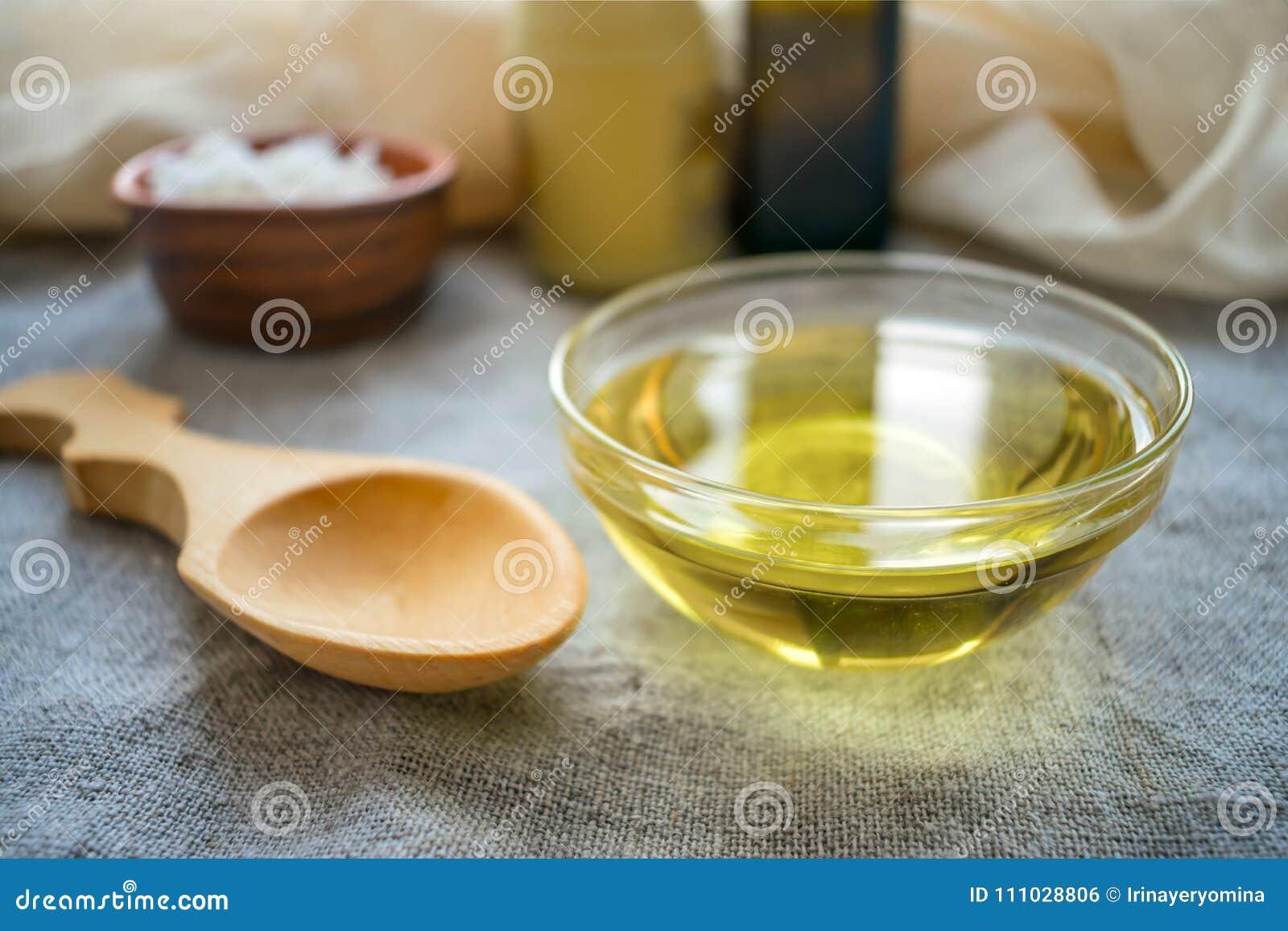 Huile liquide de la noix de coco MCT dans le bol en verre rond avec la cuillère en bois et