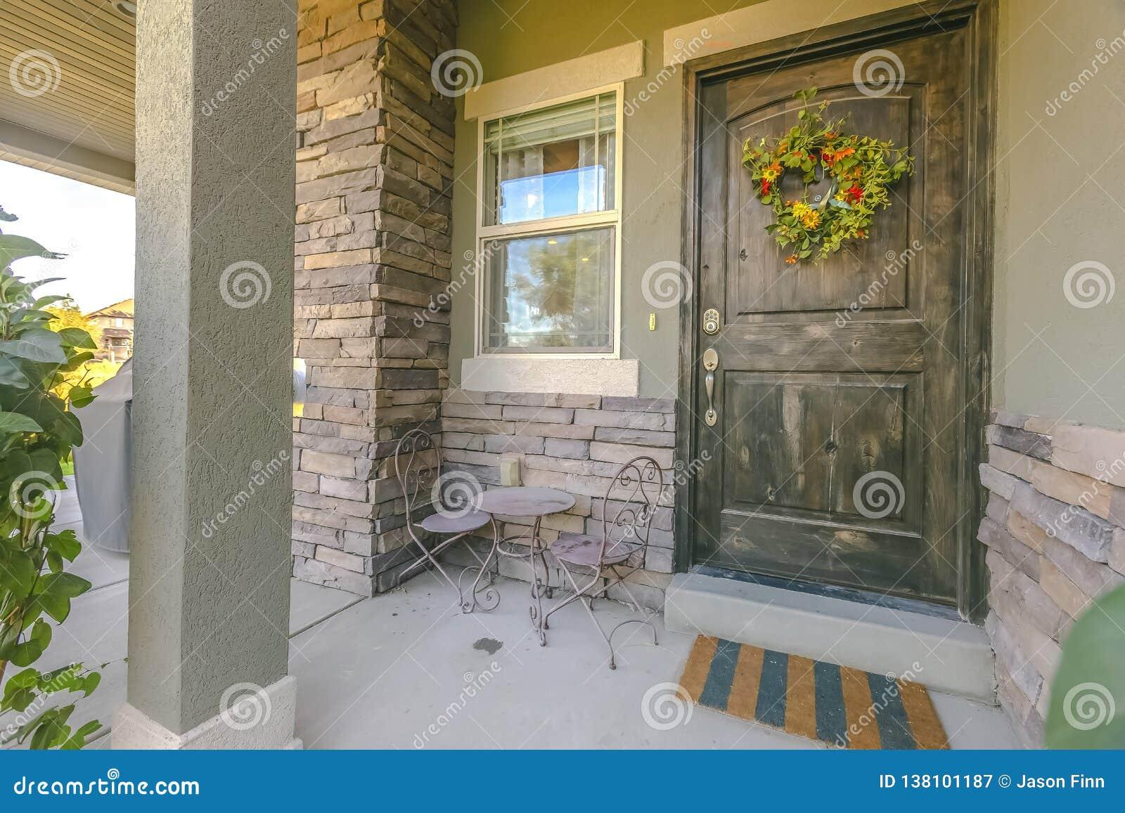 Huis met kroon op deur en meubilair op portiek