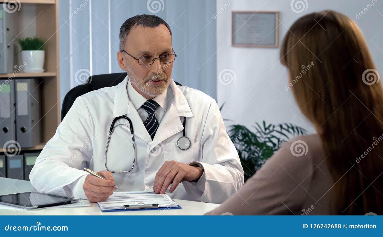 Huisarts die aan patiënt luisteren, die medische verzekering, gezondheidszorg invullen