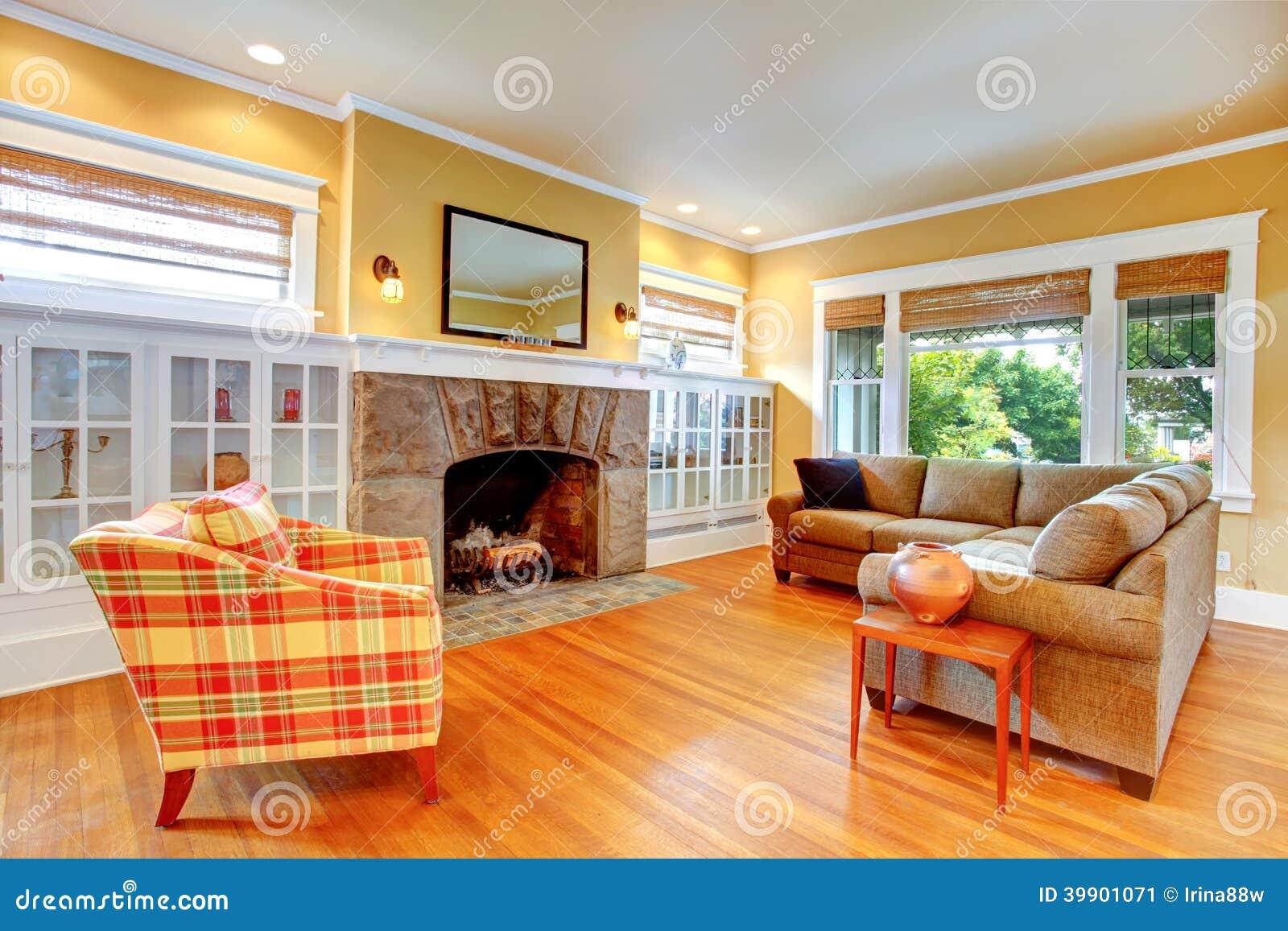 Huisbinnenland gele woonkamer met open haard stock afbeelding