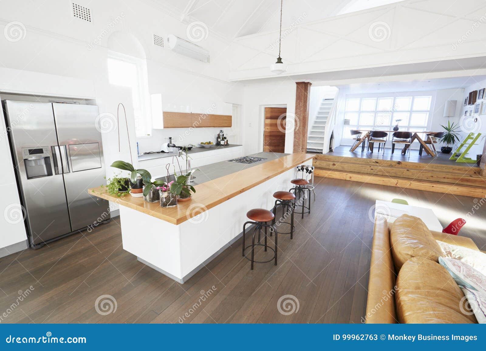 Huisbinnenland met open plankeuken en het dineren gebied stock