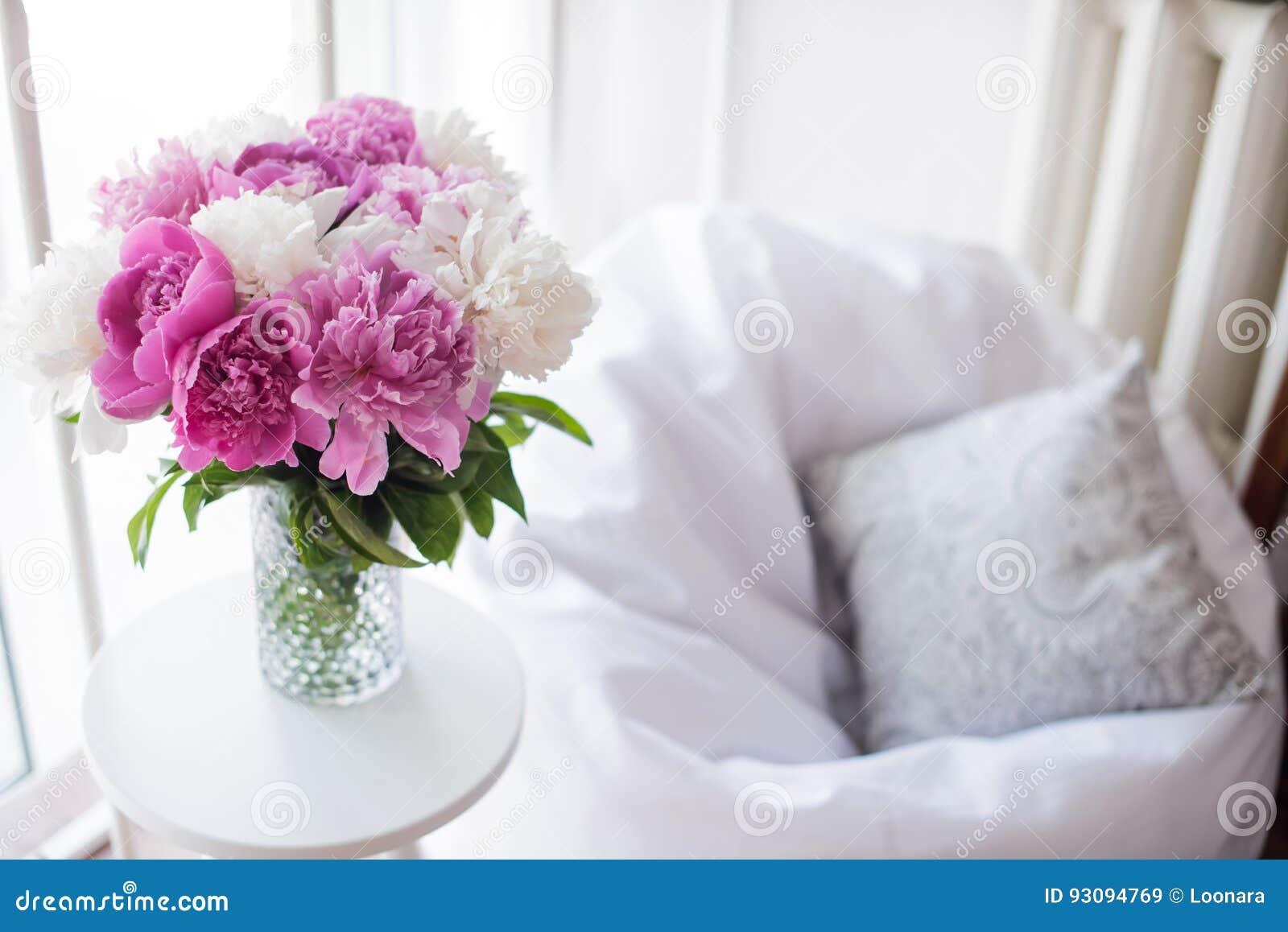 Huisdecoratie, verse roze pioenen op koffietafel in witte roo