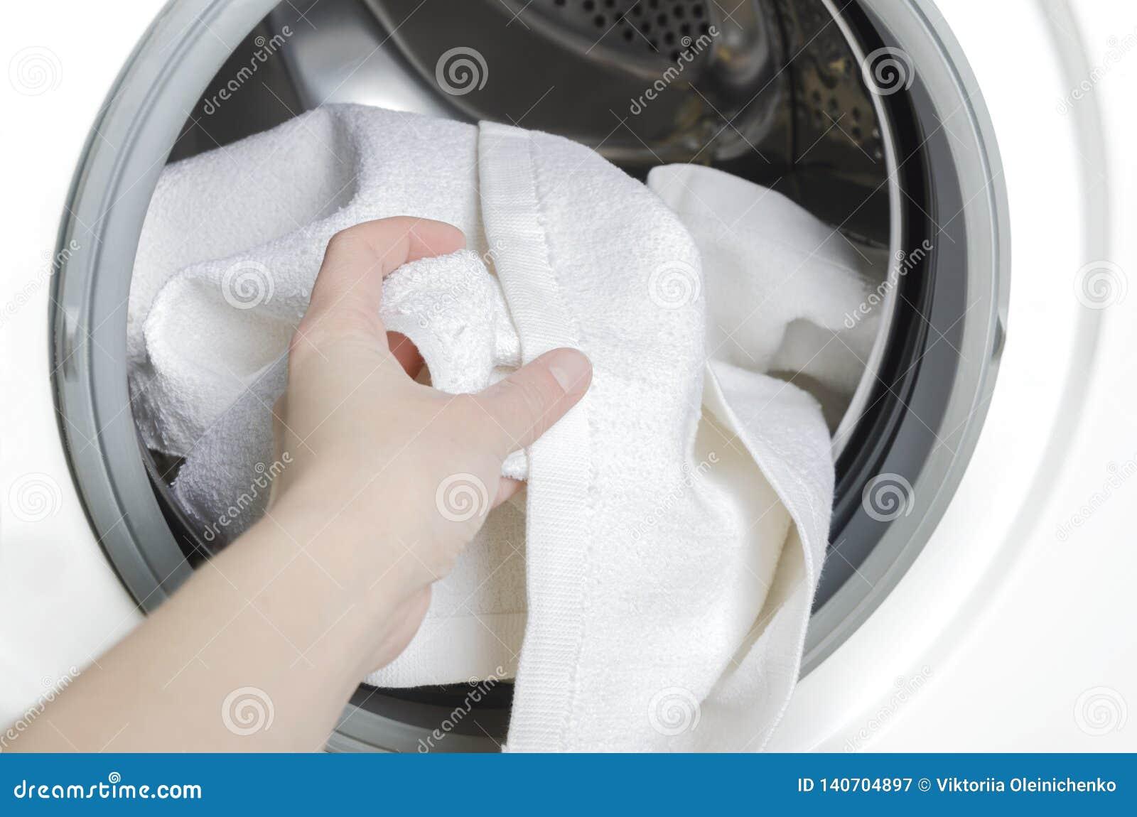 Huishoudster die schone kleren van wasmachine, close-up nemen