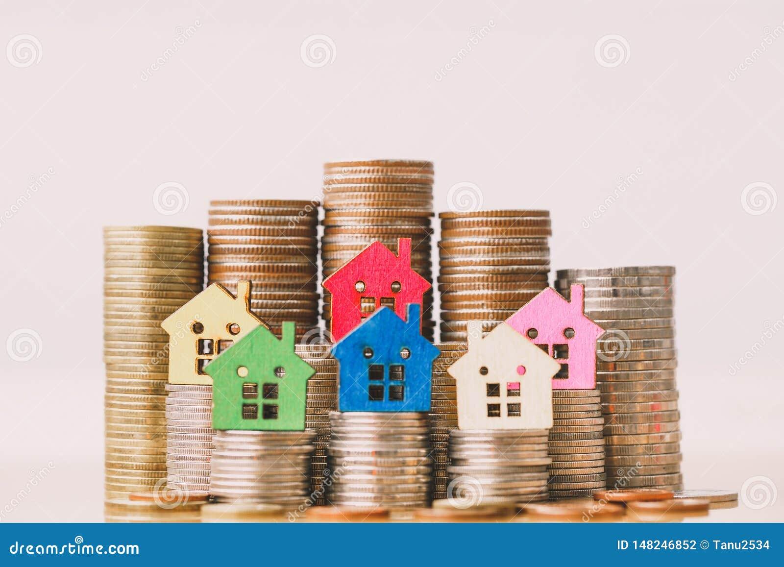 Huismodel op muntstukkenstapel De planning van besparingengeld van muntstukken om een huisconcept, een hypotheek en een onroerend