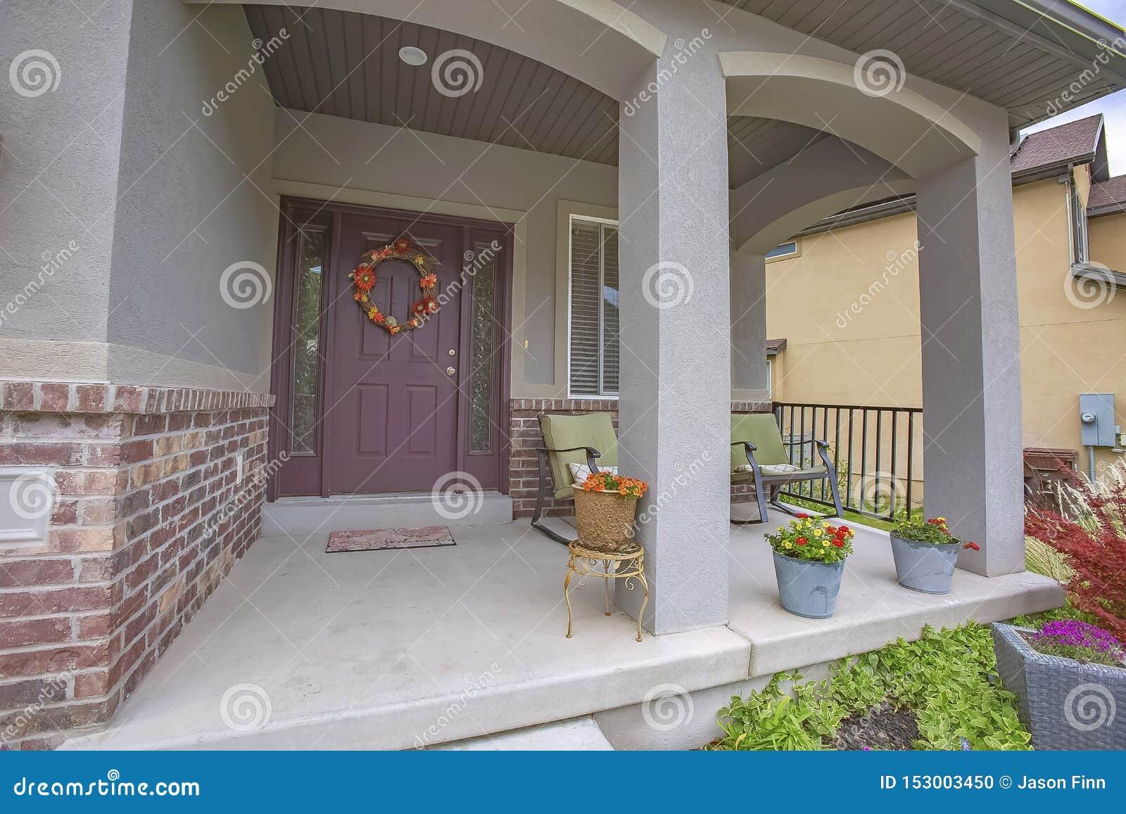 Huisvoorgevel met schommelstoelen en ingemaakte bloemen op de concrete portiek