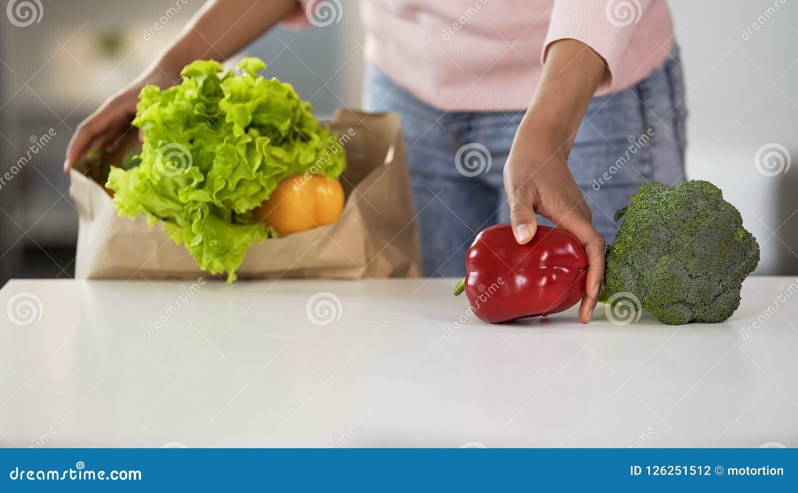 Huisvrouw die groenten op lijst van kruidenierswinkelzak zetten, gezonde voeding