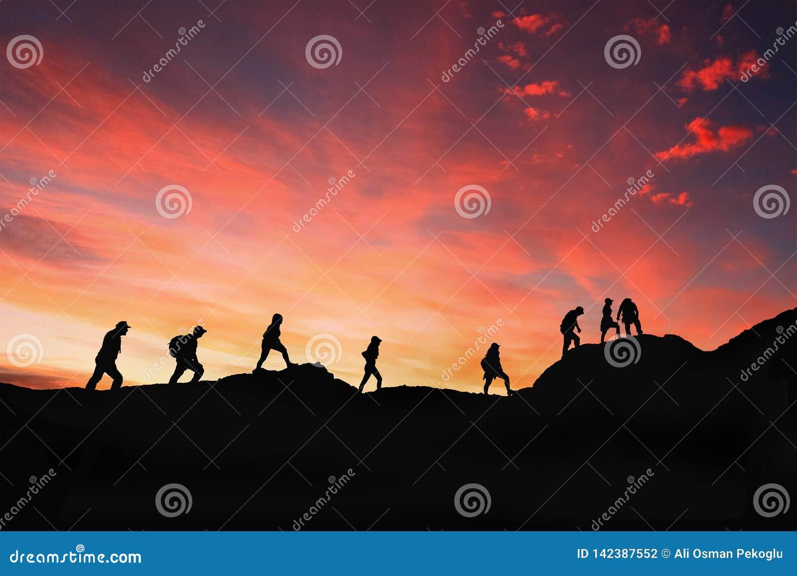 Huit amis marchent sur le chemin de montagne dans le coucher du soleil