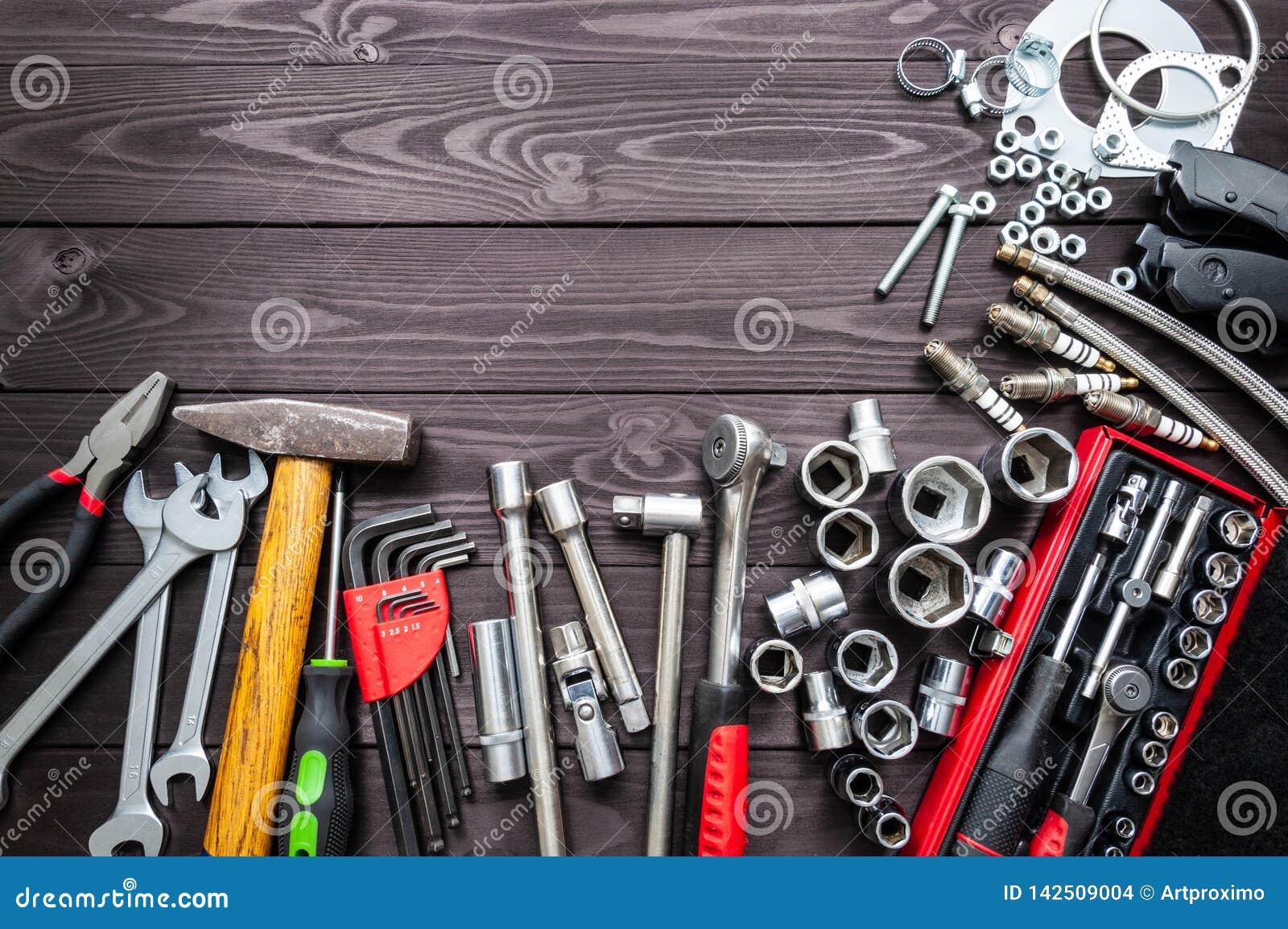 Hulpmiddelen en autovervangstukken op houten werkbank De ruimte van het exemplaar