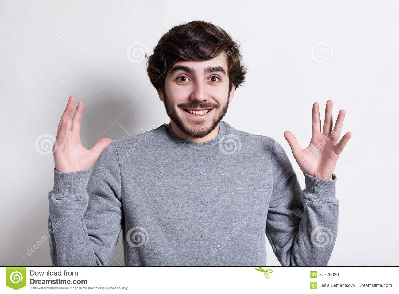 Human face expressions and emotions. Portrait of young hipster with beard and modern hairstyle smiling at camera with arms outstre
