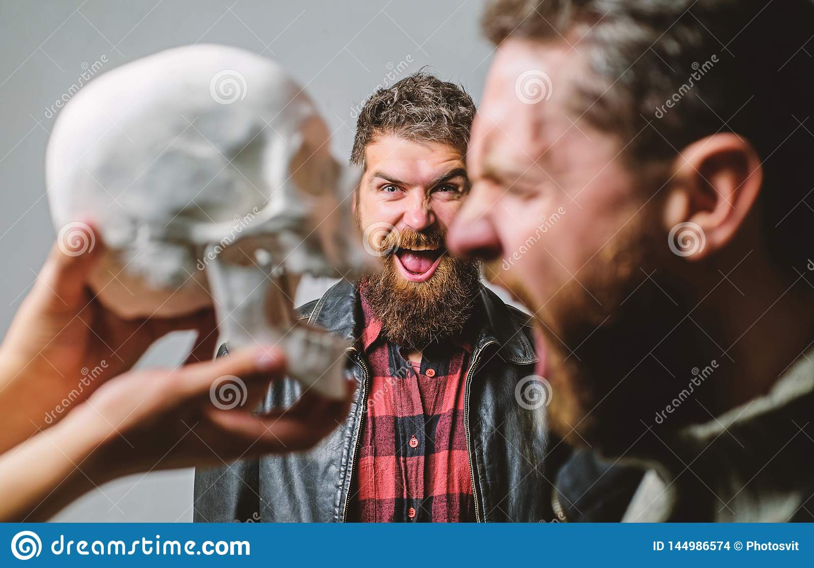 Human fears and courage. Looking deep into eyes of your fear. Man brutal bearded hipster looking at skull symbol of