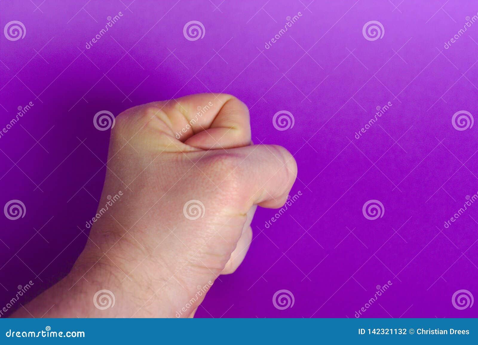 Human fist on purple background