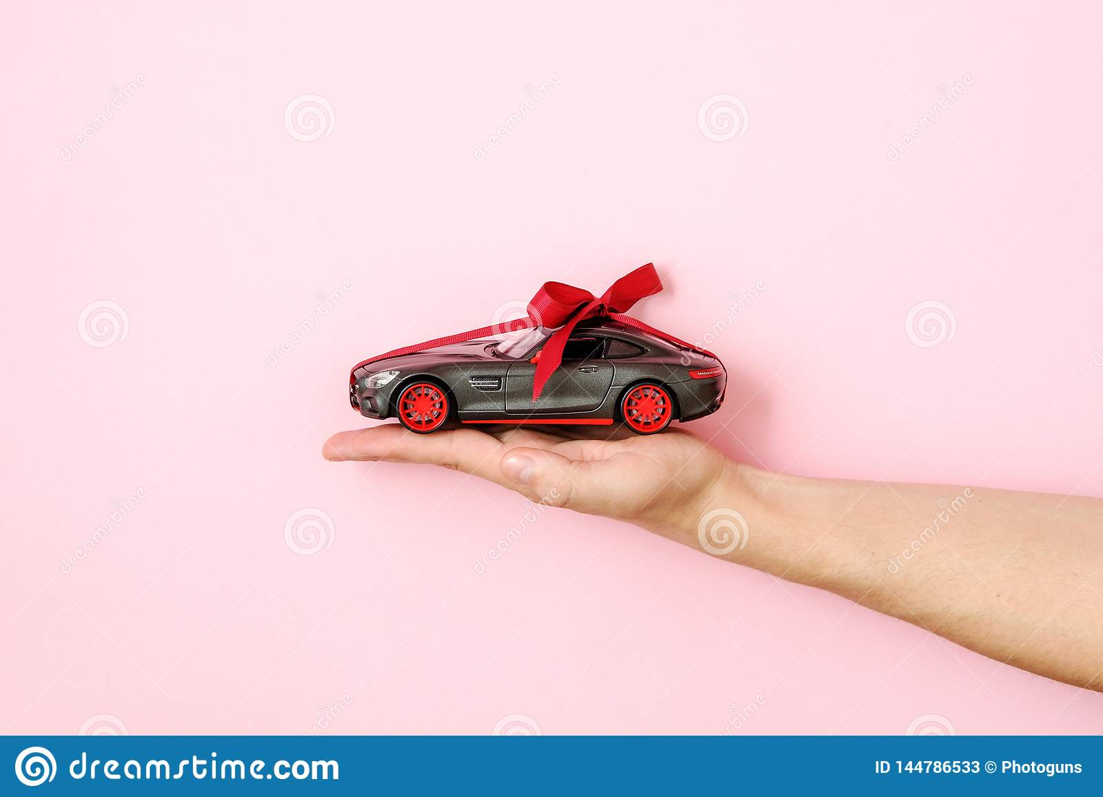 Human Hand Holding Toy Car Model Tied With A Red Ribbon And Bow On