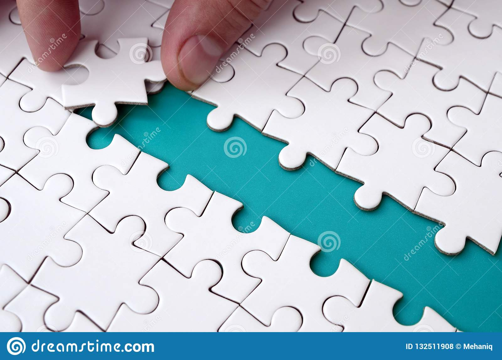 The human hand paves the way to the surface of the jigsaw puzzle, forming a blue space. The concept of overcoming the difficulties
