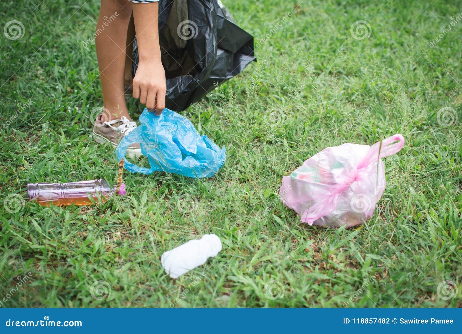 Human Hand Picking Up Plastic Into Bin Bag On Park Stock Photo