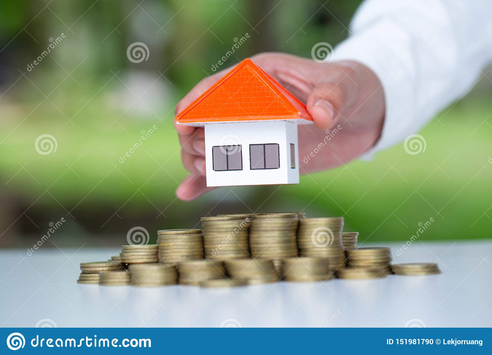 Human hand putting house model on coins stack, planning savings money of coins to buy a home concept, mortgage and real estate