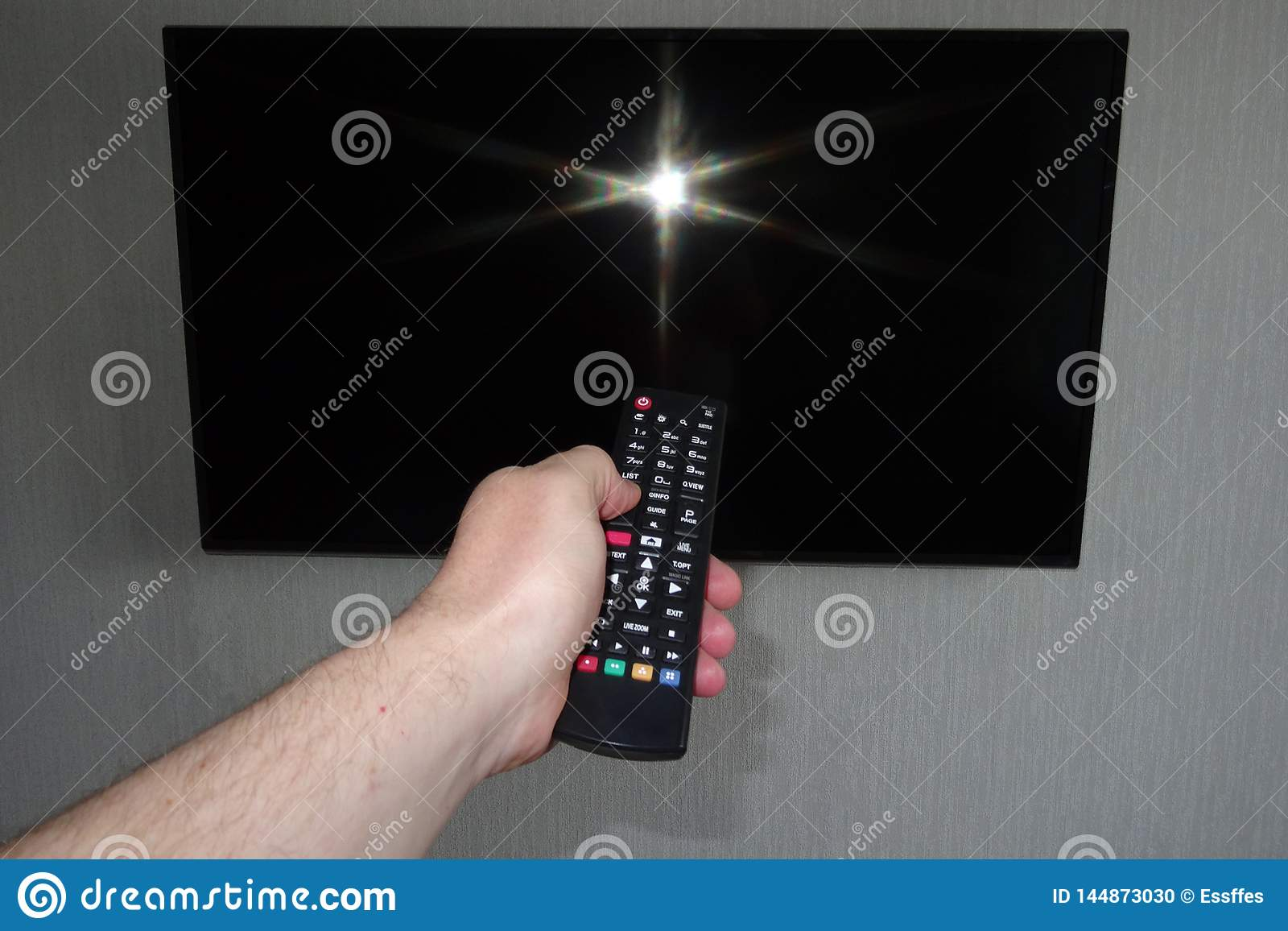 Human hand with a remote control in front of a black tv ice