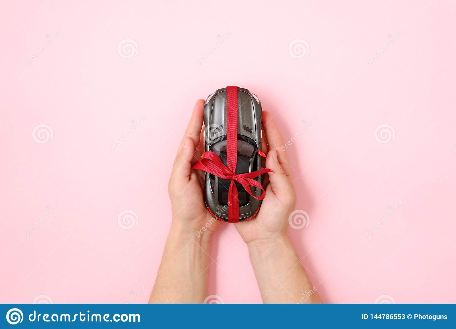 Human hand holding toy car model tied with a red ribbon and bow on pink background. Car insurance services, car for sale, special