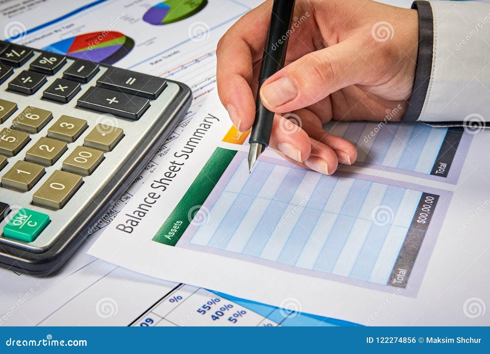 write in balance sheet summary stock photo image of hand