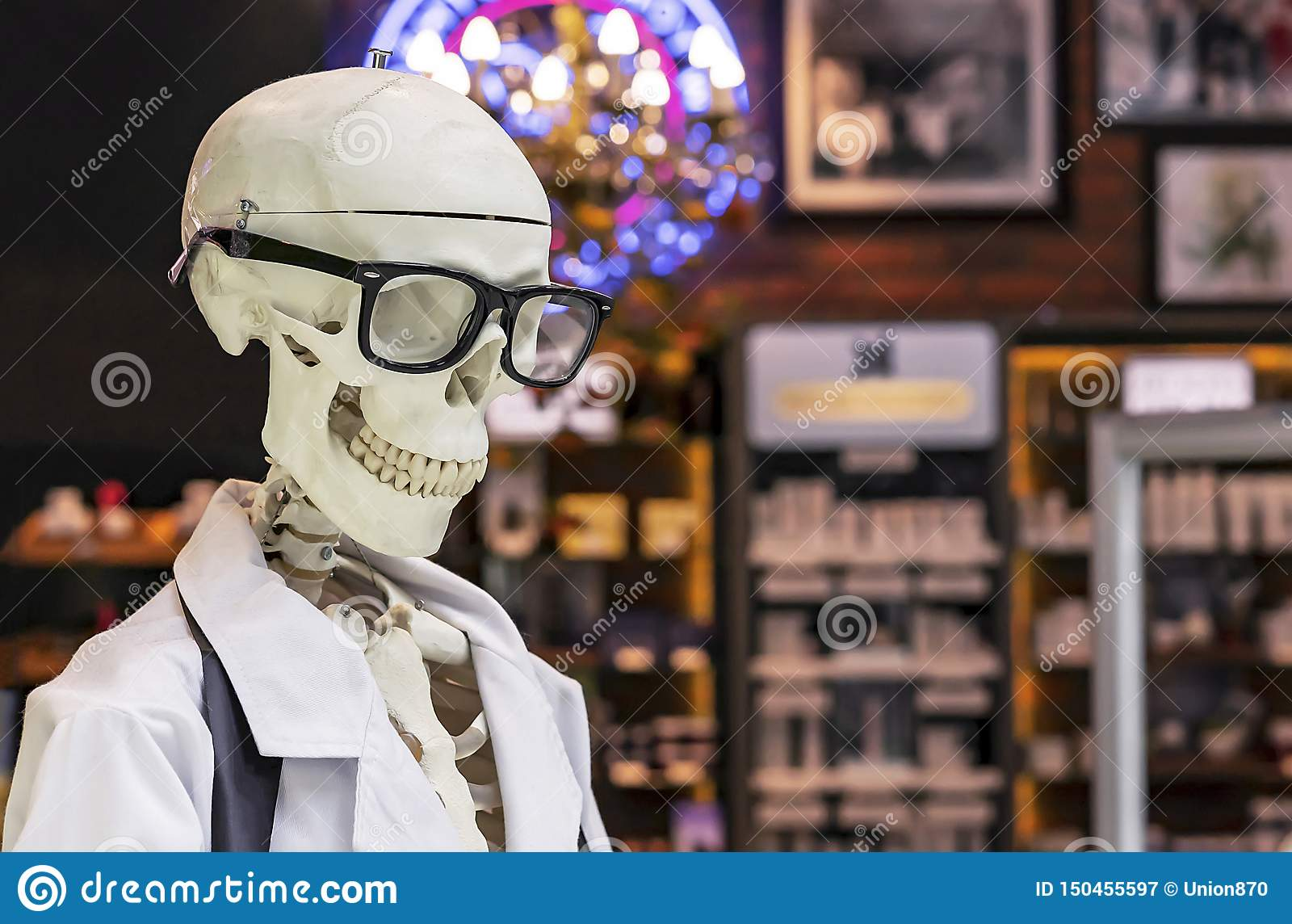 Human skeleton in a white medical gown and black glasses