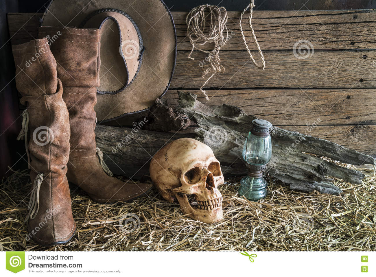 Human skull and cowboy boots in barn background