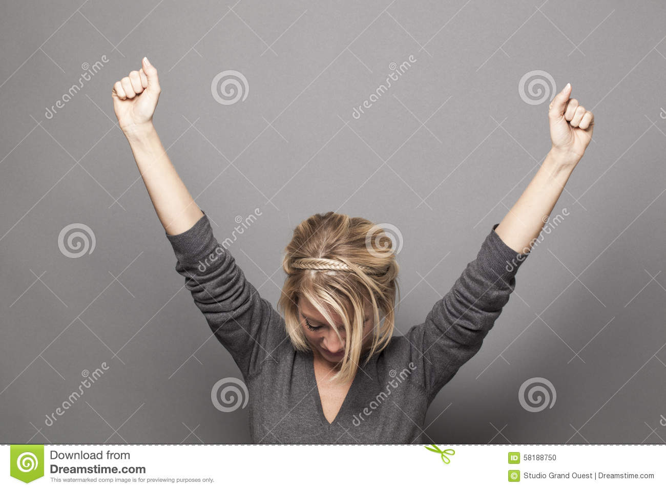 Humble 20s blonde woman raising hands for victory