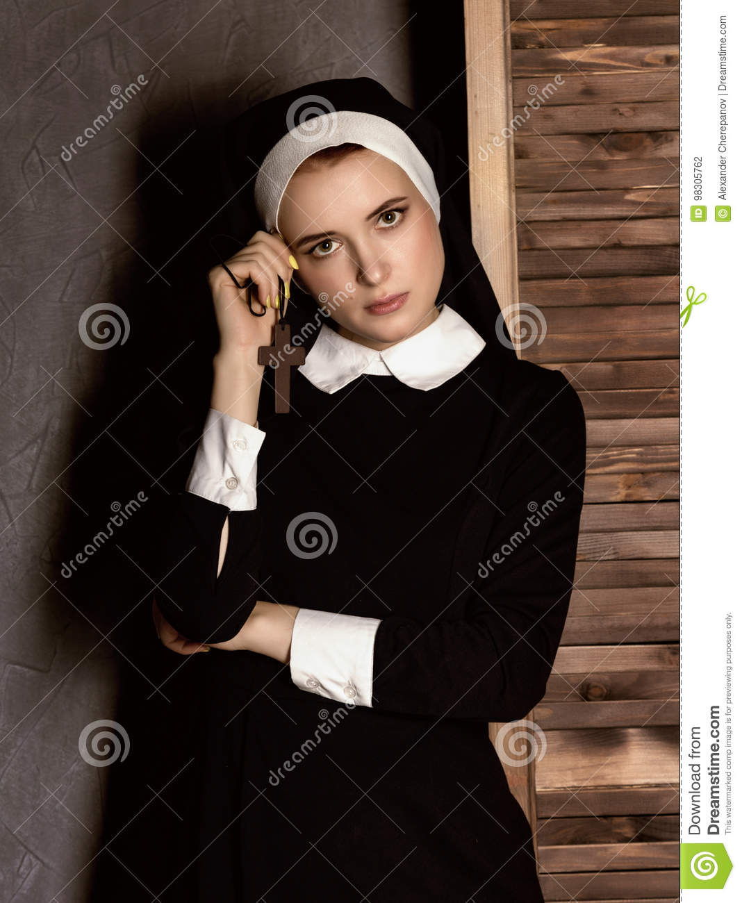 humble young beautiful nun in robes holding a cross on a grey