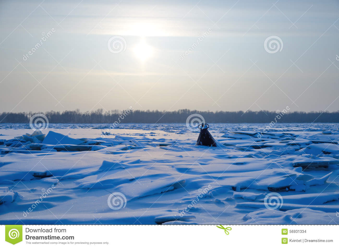 The hummocks and the buoy on the river in winter under the sun