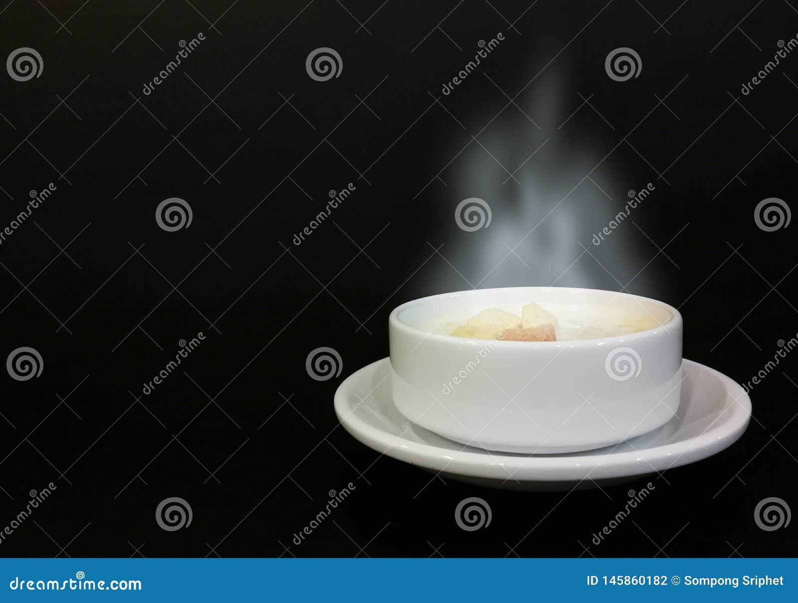 Humo de la sopa del maíz caliente en una taza blanca